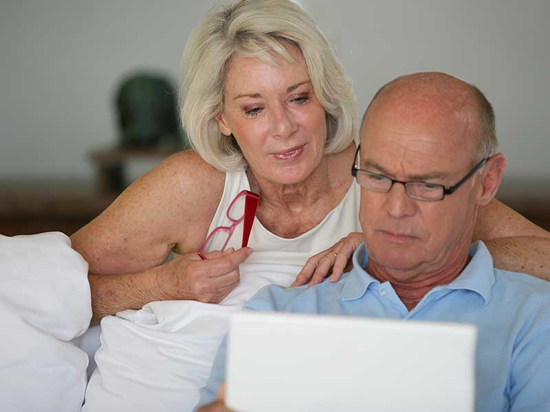 couple de retraités regardant un ordinateur portable